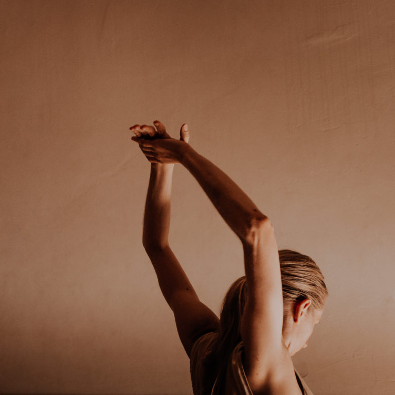Dancer woman stretches arms above head in front of terracotta wall