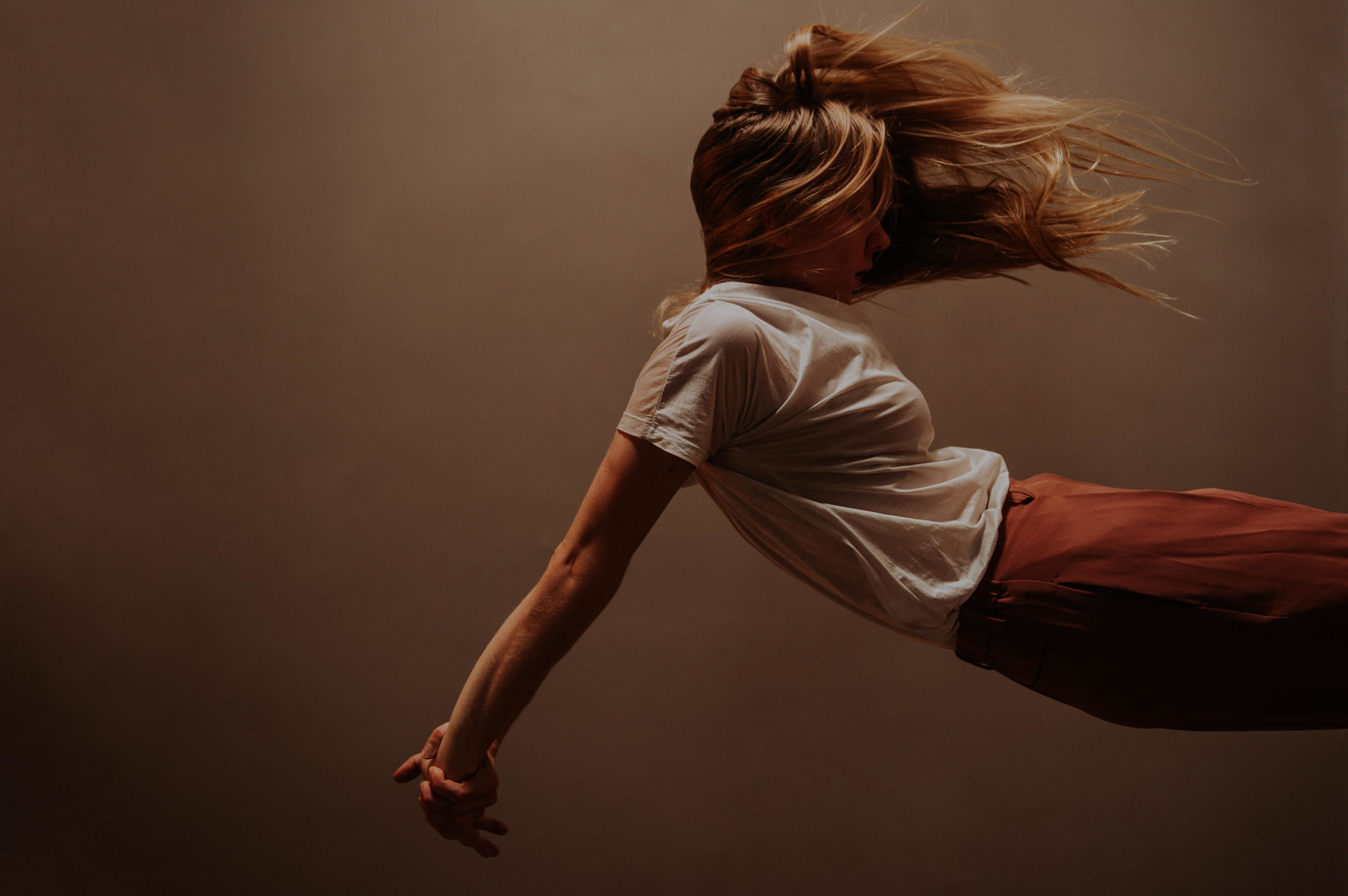 Woman in white tee shirt and orange pants does a backward dive into the frame from the right-hand side. Her amber hair is windswept.